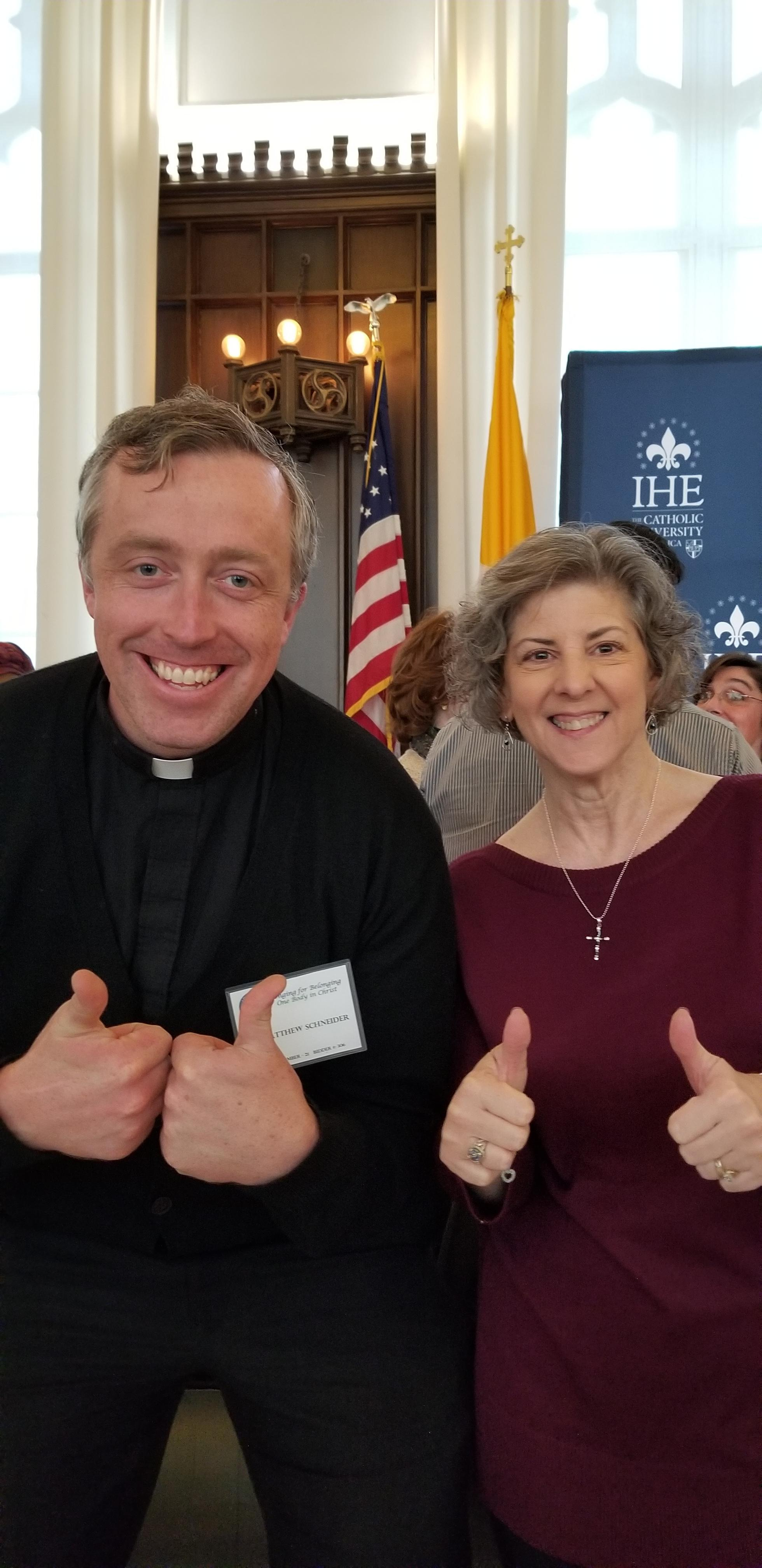 "Father Matthew Schneider and Charleen Katra giving two ""thumbs up"""