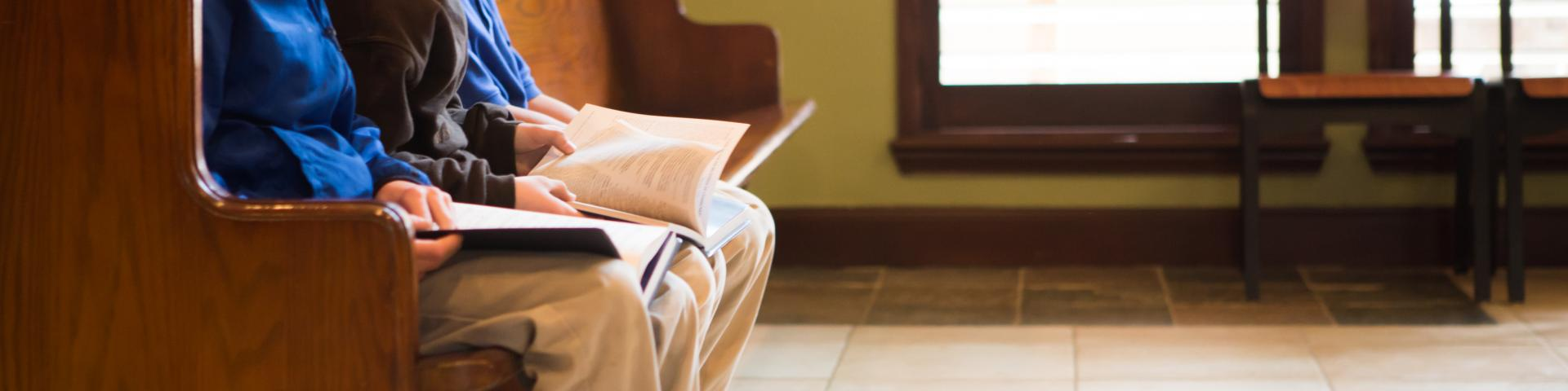 cropped image of boys in a pew reading a ther missalettes