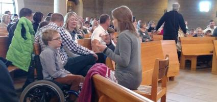 A sign language interpreter and a child in a wheel chair at Mass