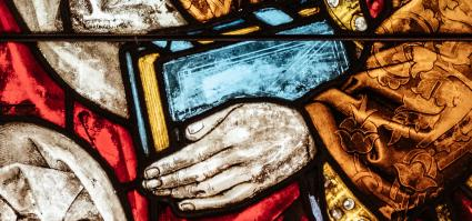 close-up of a stained glass window: a man holding a book