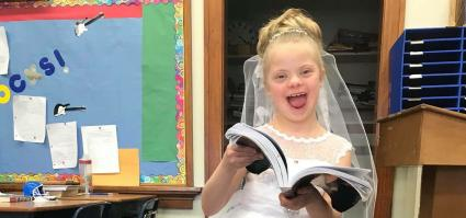 Raylee smiling at the camera in her first communion dress with her first communion book