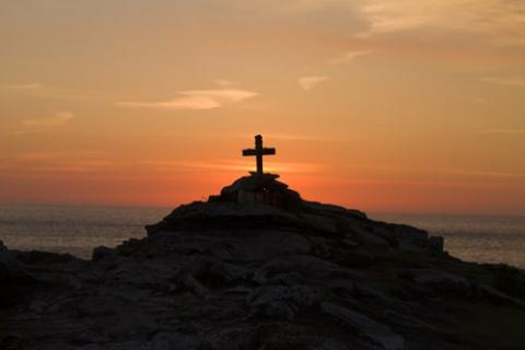 Cross on a hill with a sunset in the background