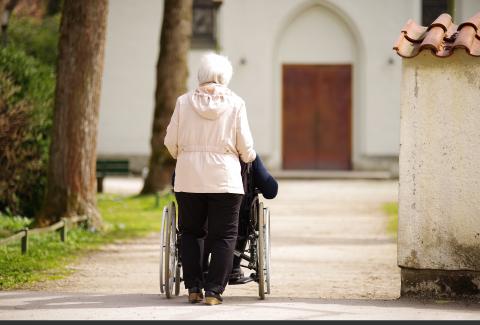 Woman pushes person in wheelchair toward church