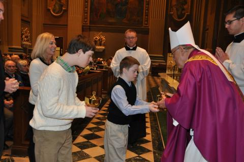 Two children handing the gifts of bread and wine to the Bishop during Mass. One of them has down syndrome.