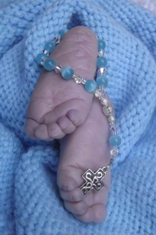 Baby's feet with rosary