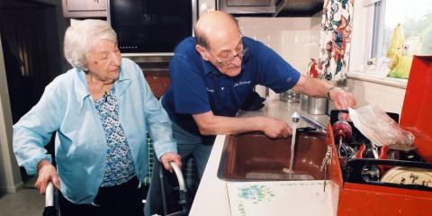 Picture of a husband helping his wife in the kitchen. Wife has a walker.