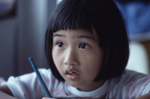 Child sitting with a pen at a desk looking up