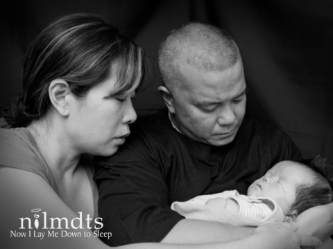 Black and white photo of a father and mother holding and looking at their infant child.