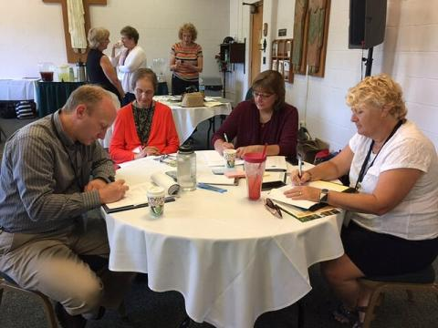 Four people working at a table during a conference