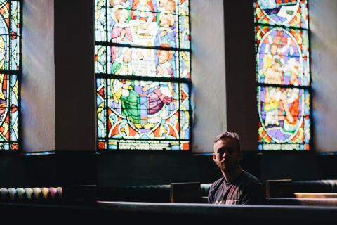 Picture of young adult male sitting in a pew in a dark church with stained glass weekends in the background