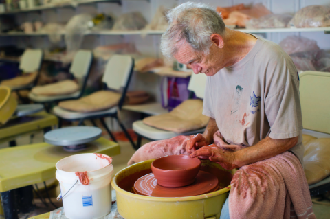 Martin making pottery with a pottery wheel