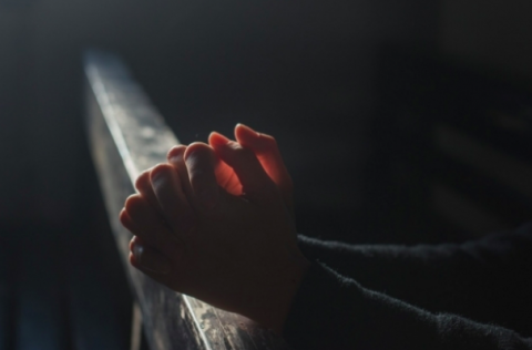 A person's hands folded in prayer