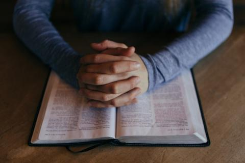 A person's hands folded in prayer on top of a bible