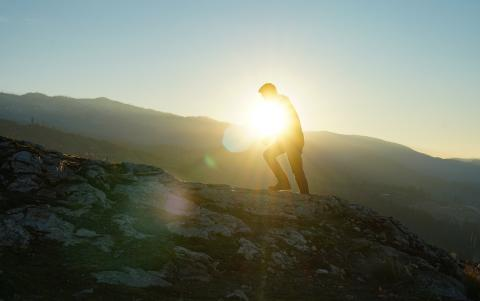 The silhouette of a person climbing on a mountain with the sun in the background