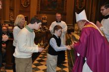 A person with down syndrome giving the gifts to a bishop