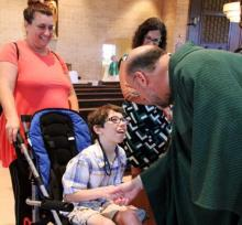 Priest shaking the hand of a child who uses a wheelchair