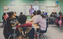 Students at their desks watching their teacher teach