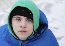 A boy in a winter setting looking at the camera
