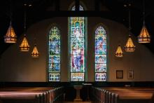 Dark church with three stained glass windows and 3 golden stained glass chandeliers hanging on each side